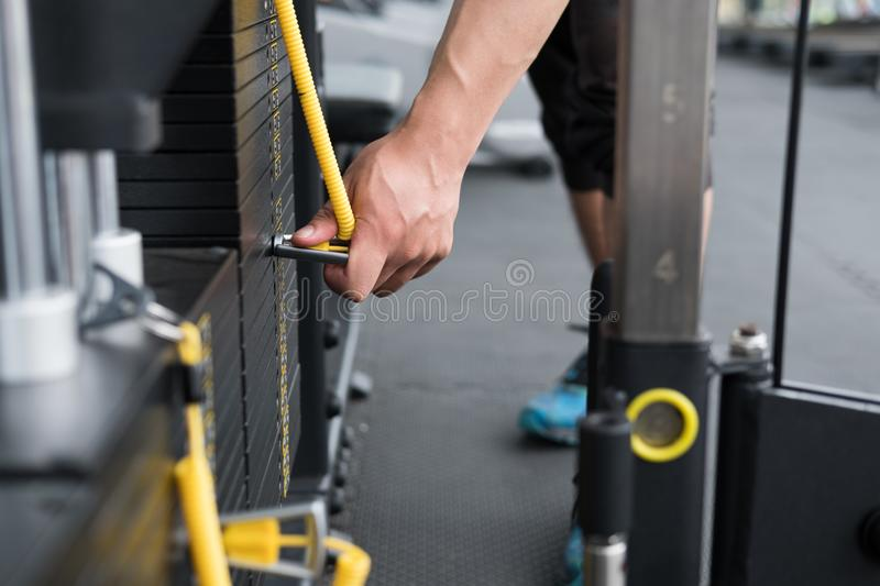 young man execute exercise with pull down machine in fitness center. male athlete select weight for training in gym. sporty guy w stock image
