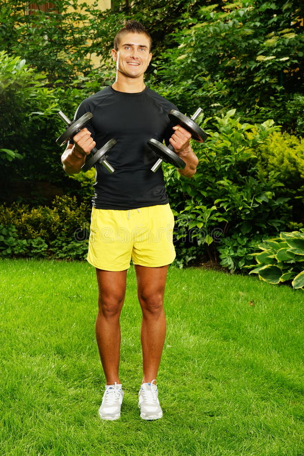 Young man exercisess with dumbells. Young man exercising with dumbbells outdoor in garden royalty free stock photo