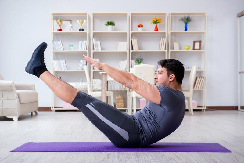 Young man exercising at home in sports and healthy lifestyle con royalty free stock photos