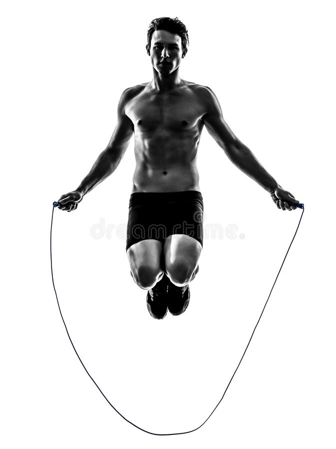 Young man exercising jumping rope silhouette. One caucasian man exercising jumping rope in silhouette studio on white background stock photo