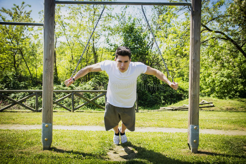 Young man exercising outside in city park. Attractive young man exercising and working out in outdoor gym in city park stock photos