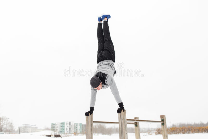 Young man exercising on parallel bars in winter royalty free stock photography