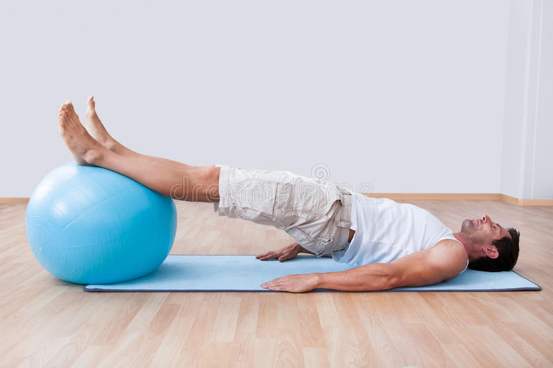 Young Man Exercising On A Pilates Ball stock image