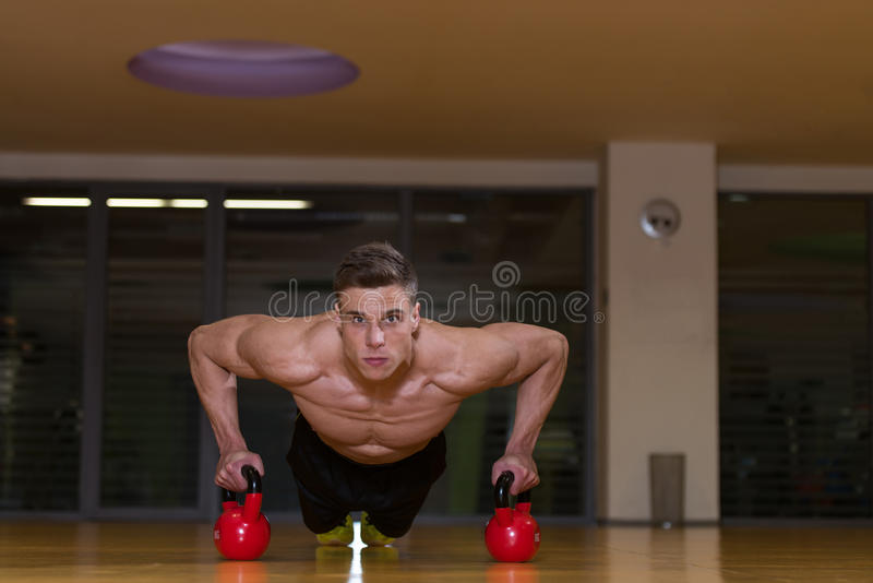 Young Man Exercising Push Ups On Kettle Bell royalty free stock photos