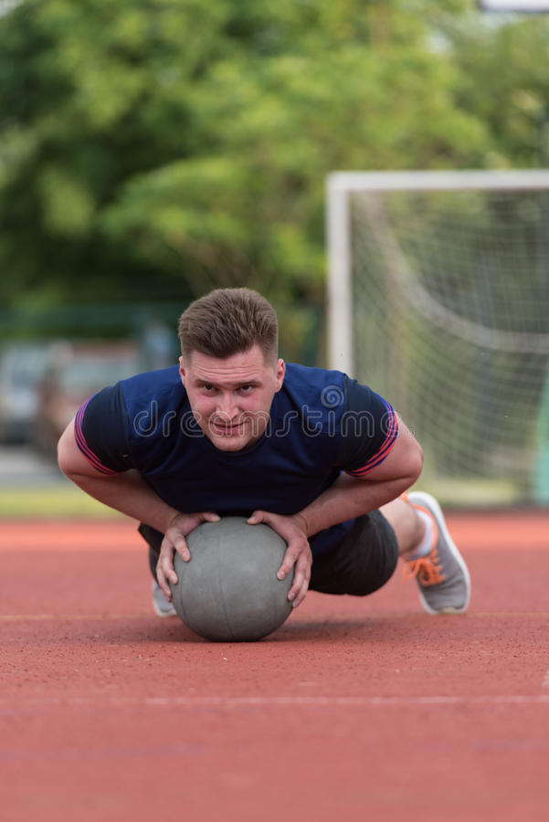 Young Man Exercising Push-Ups On Medicine Ball Outdoor. Young Man Outdoors Performing Push Ups On Medicine Ball Bodybuilding Exercise royalty free stock images