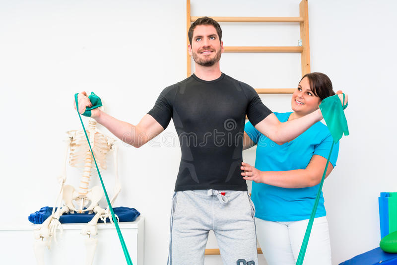 Young man exercising with resistance band in physical therapy. Young men exercising with resistance band in physical therapy with personal therapist royalty free stock photos