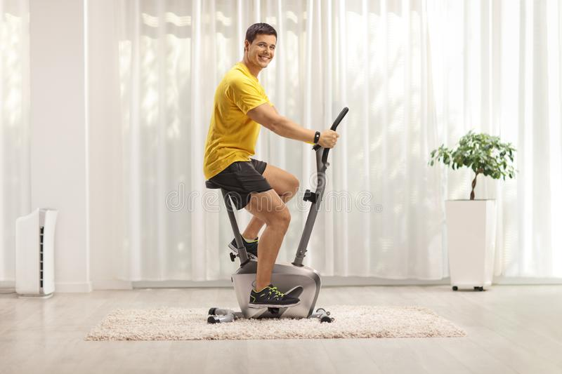 Young man exercising on a stationary bike stock photo