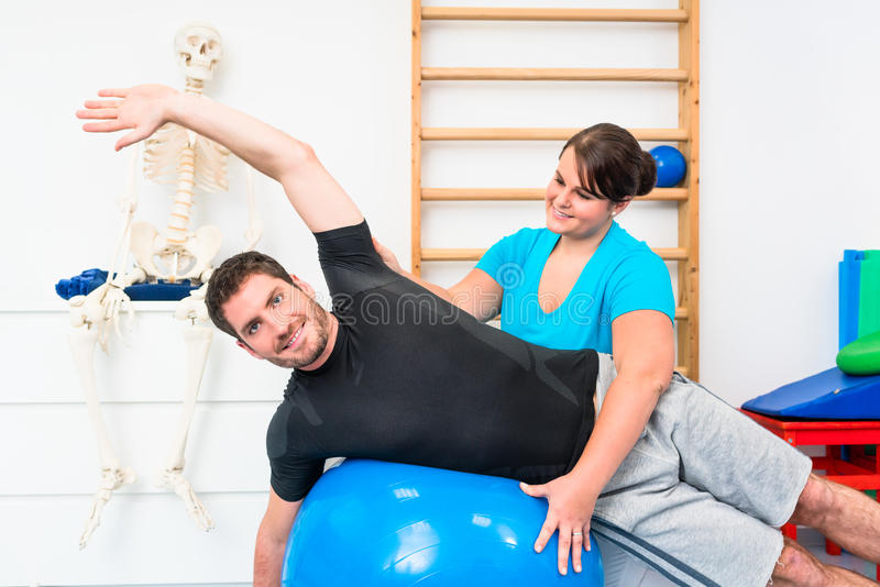 Young man exercising on swiss ball in physiotherapy stock photos