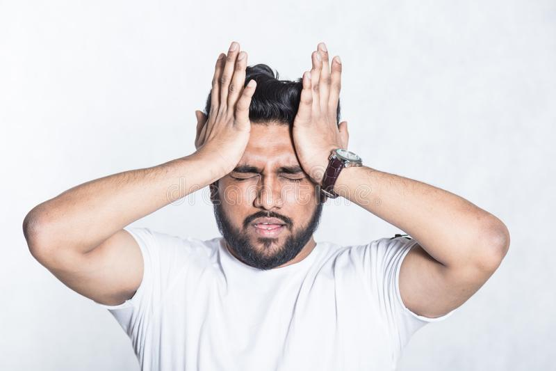 Young man experiencing head hurts, looking miserable and exhausted. stock photography