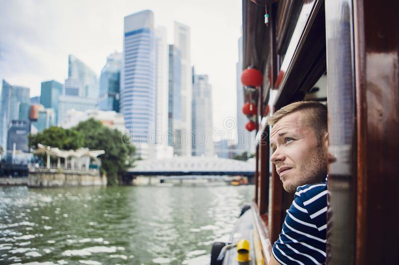 Young tourist exploring city. Young man exploring city and looking out from river boat in Singapore stock photos