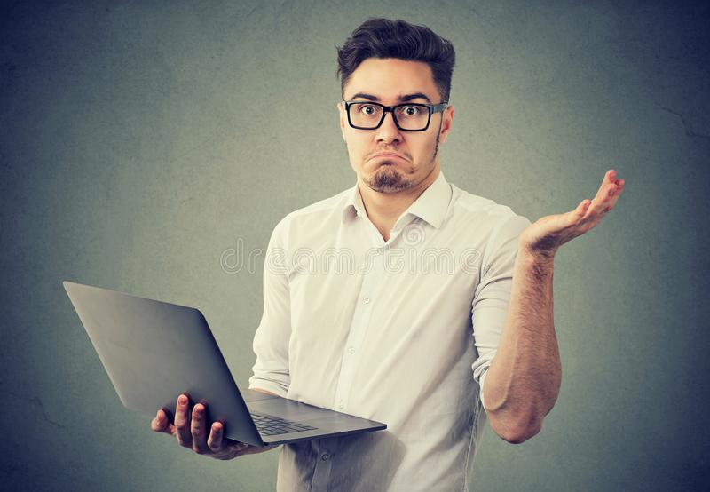 Perplexed young man with laptop royalty free stock photo