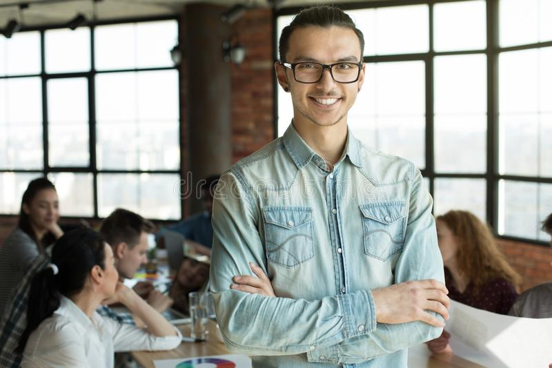 Young man in eyeglasses smiling at camera at meeting stock photo