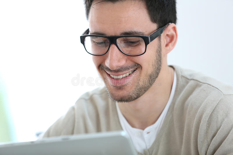 Young man with eyeglasses using tablet. Young man with eyeglasses websurfing with tablet royalty free stock photo