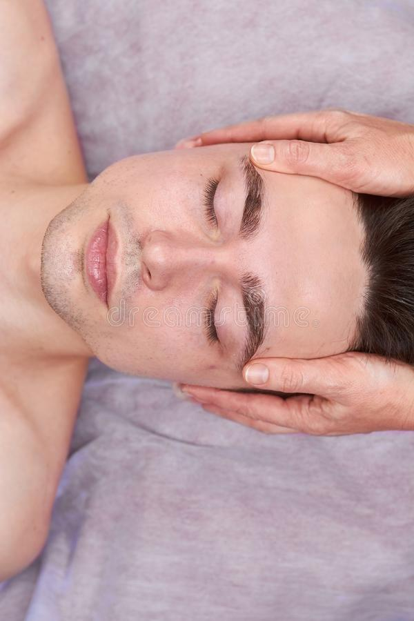 Young man, facial massage. royalty free stock images