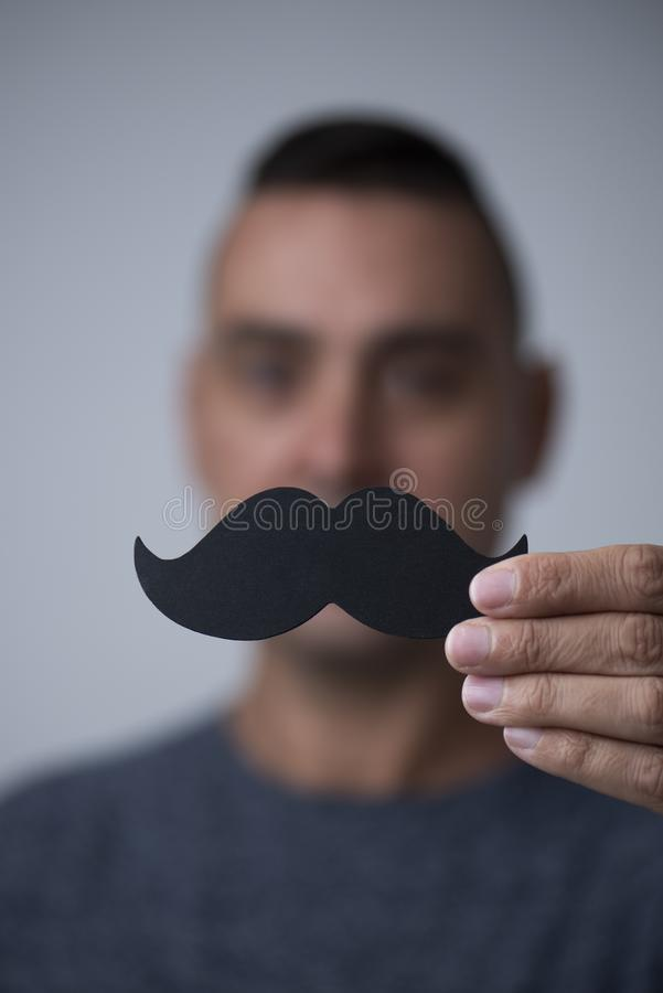 Young man with a fake moustache. Closeup of a young caucasian man holding a fake moustache in front of his face stock images