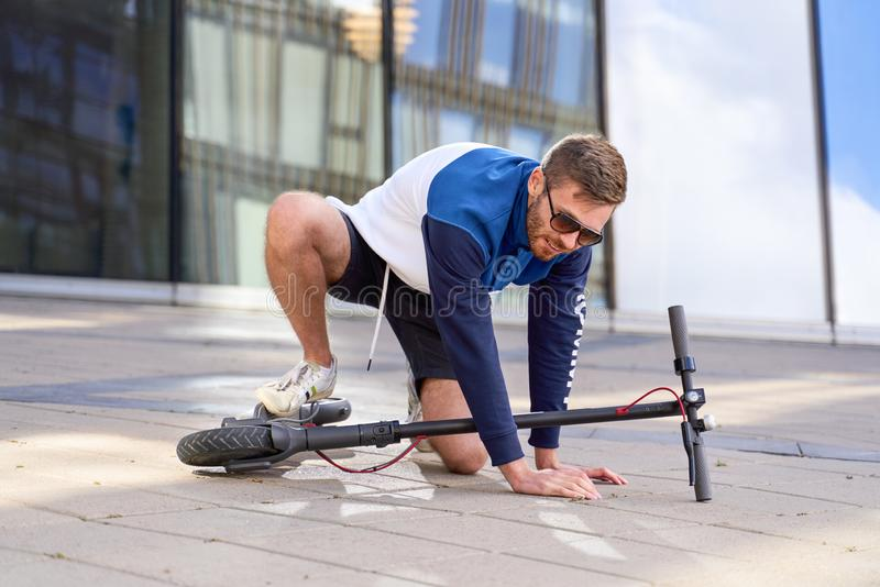 Young man falls during training on his scooter. royalty free stock photo
