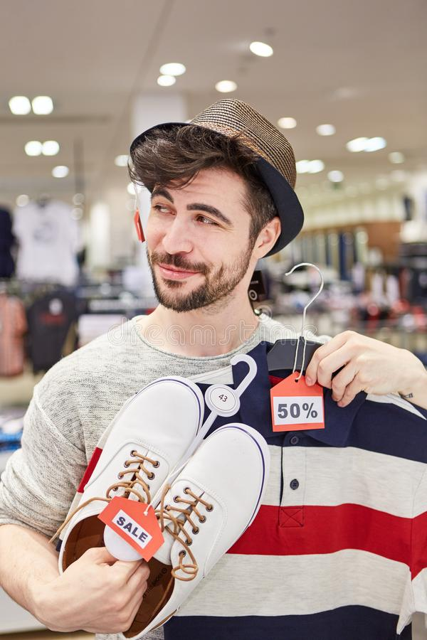 Young man finds special offers. Young man in fashion shop finds special offers while shopping for fashion stock photography