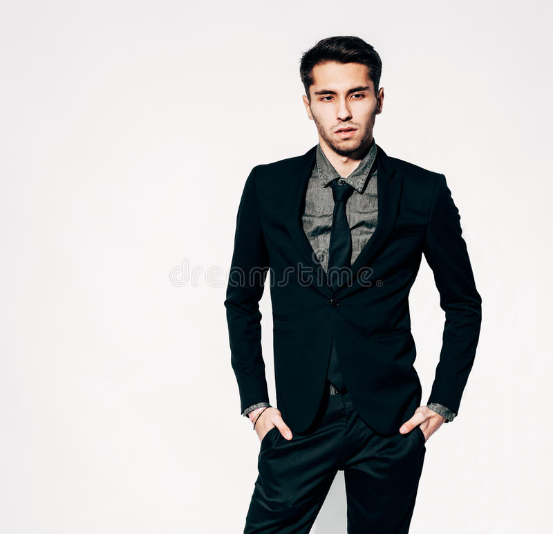 A young man in a fashionable suit posing. Indoor. Warm color. stock photography