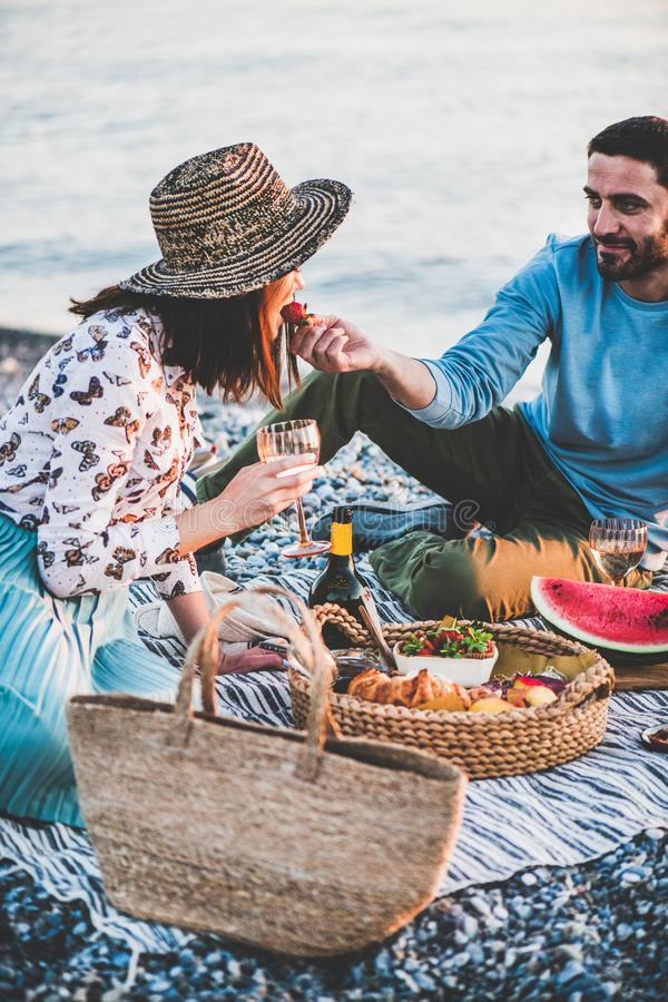 Young man feeding woman with strawberry during summer picnic stock photo