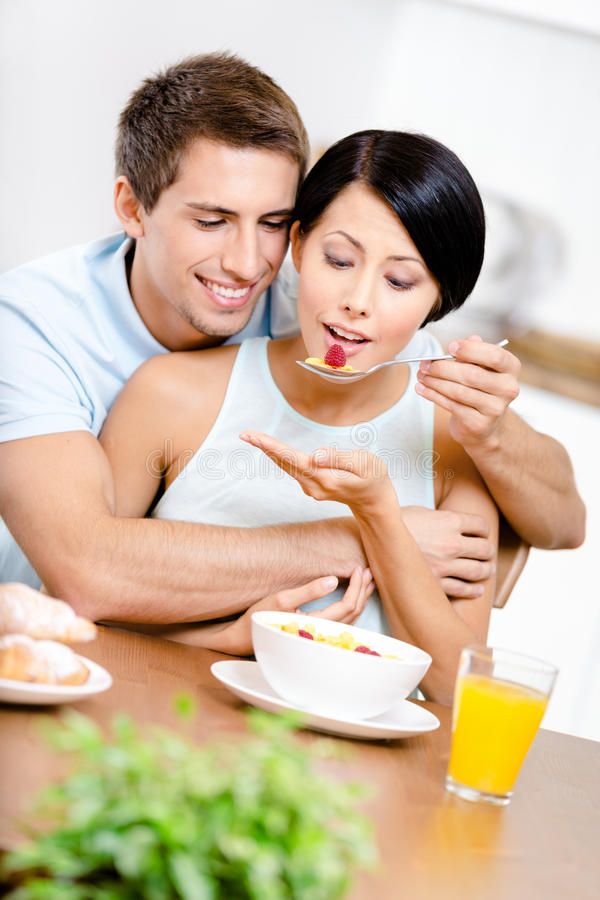 Young man feeds and hugs his girlfriend