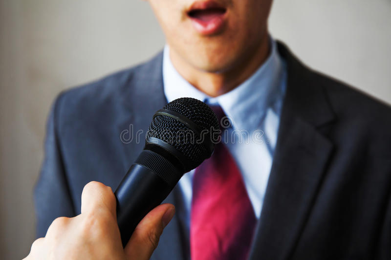 Young man feeling awkward getting asked by a journalist on isolated white background royalty free stock photography