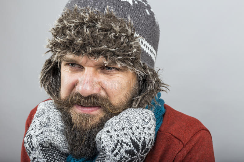 Young man feeling cold trying to keep warm, shaking and shivering, wearing gloves and knitted scarf royalty free stock photography