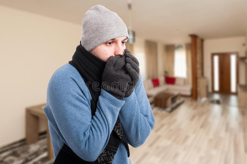Young man feeling cold and warming his hands stock photography