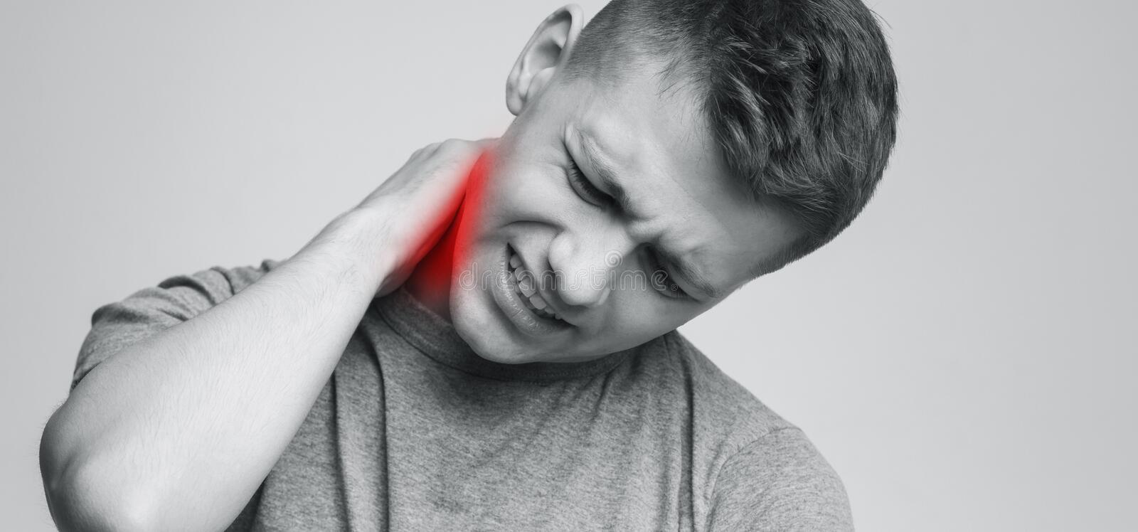 Young man feeling exhausted and suffering from neck pain. Black and white panorama photo, empty space stock photo