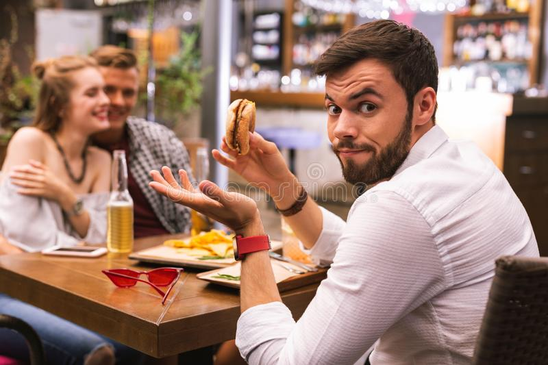 Young man feeling surprised while noticing his friends flirting. Why. Emotional men with tasty burger feeling surprised while noticing his best friends flirting royalty free stock photos
