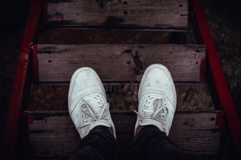 Young man feet in front of the red wood stairs down stock images