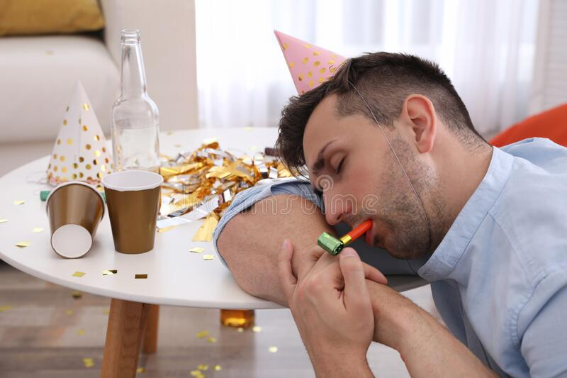 Young man in festive cap sleeping at table in room royalty free stock image