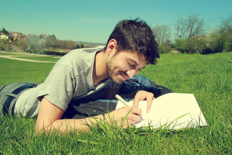 Young man in field writing royalty free stock photo
