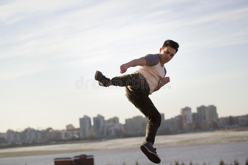 Young male kick fighter performs acrobatic kick in front of skyline stock photo