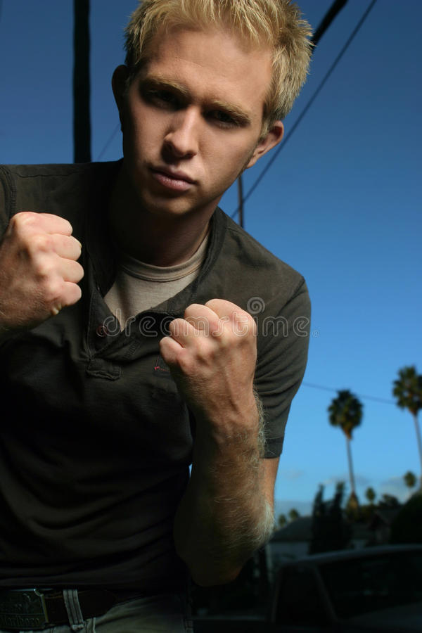 Young man fighting stock photography