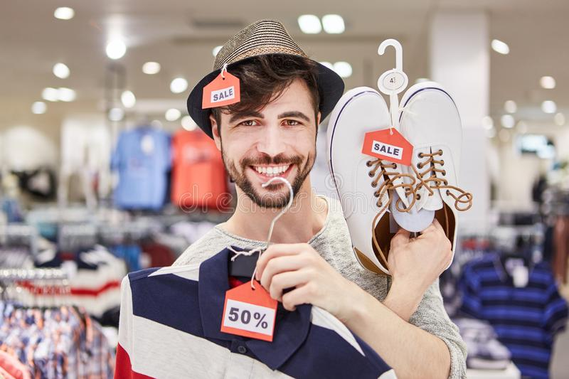 Young man finds special offers. Happy young man is finding special offers while shopping stock images