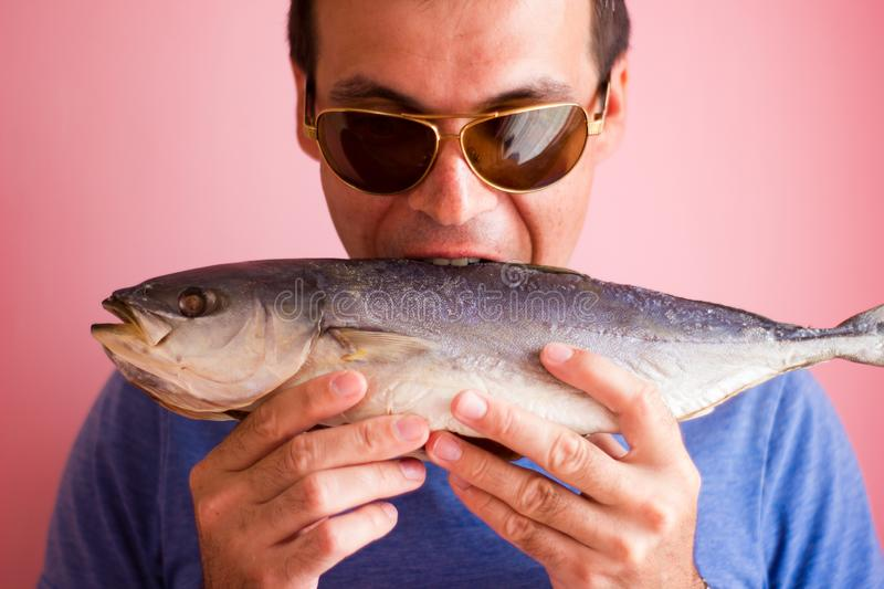 Young man with a fish in his hands - salted tuna stock photography