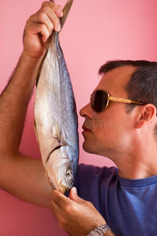 Young man with a fish in his hands - salted tuna royalty free stock photos