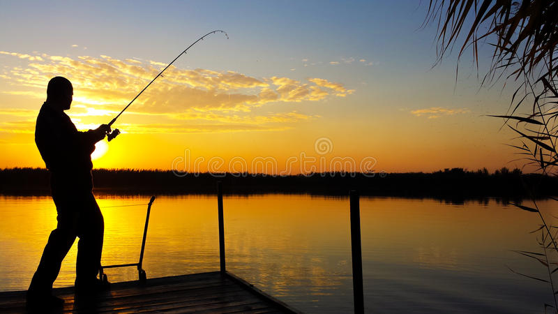 Young man fishing on a lake at sunset stock images