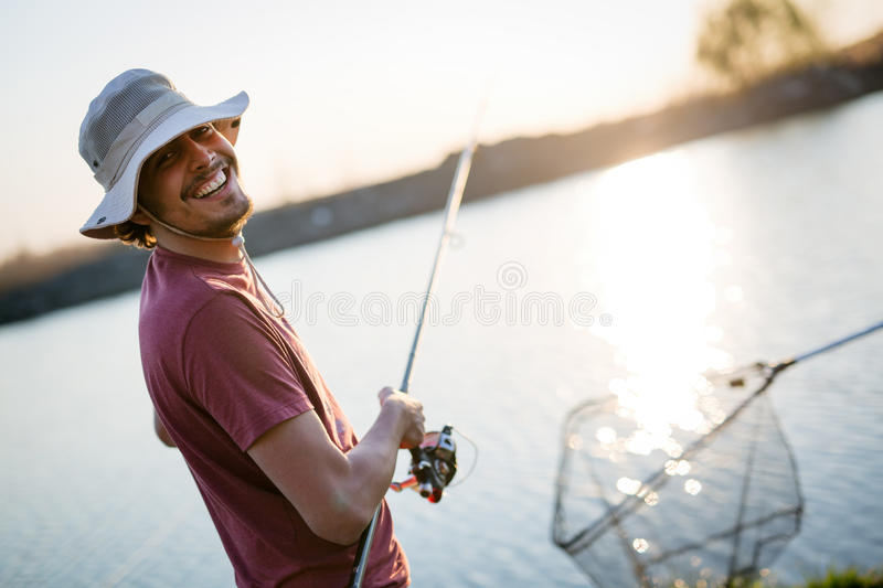Download Young Man Fishing On A Lake At Sunset And Enjoying Hobby Stock Photo - Image: 93108380