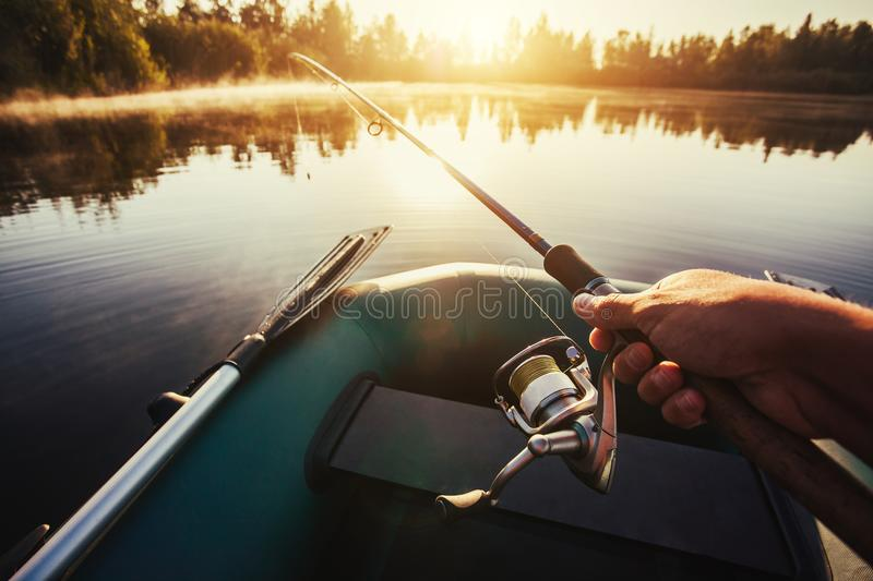 Man fishing on a lake from rubber boat. Young man fishing on a lake. view from the boat royalty free stock images