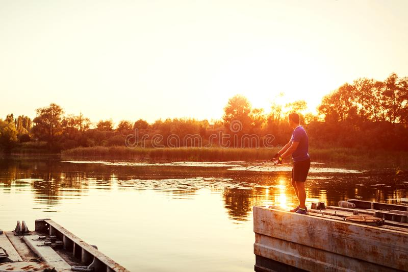 Young man fishing on river standing on bridge at sunset. Happy fiserman enjoying hobby royalty free stock photography