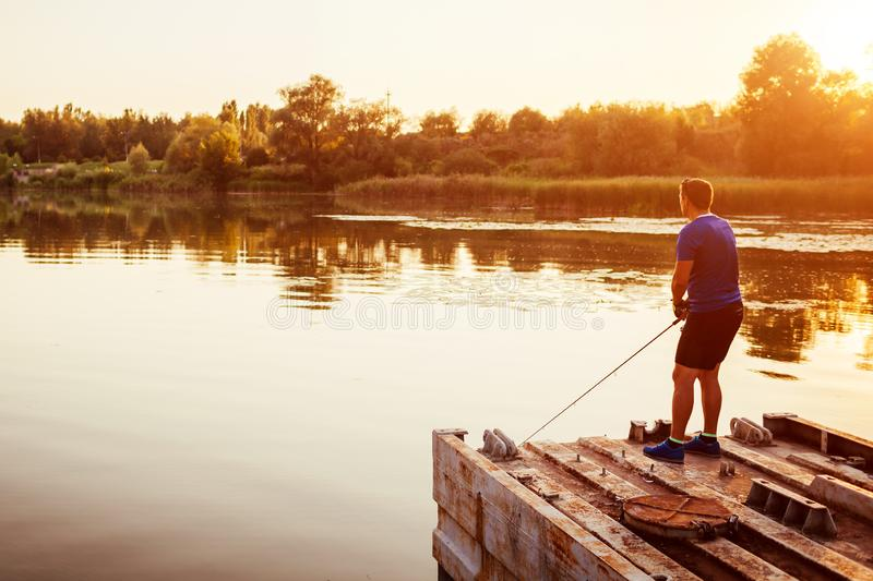 Young man fishing on river standing on bridge at sunset. Happy fiserman enjoying hobby royalty free stock photo