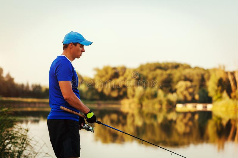 Young man fishing on summer river at sunset. Sad fiserman upset because of bad catch royalty free stock photography