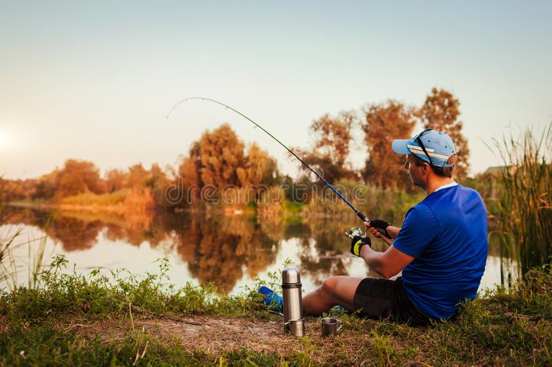 Young man fishing on river at sunset. Happy fiserman royalty free stock image