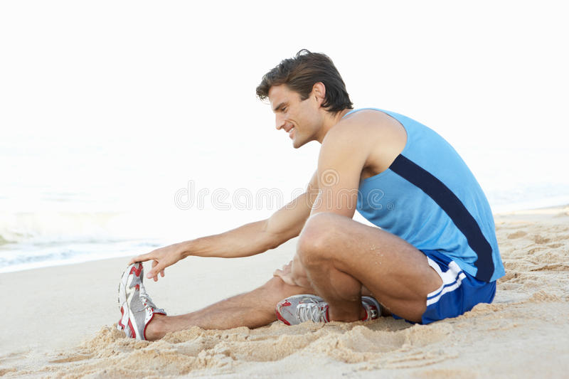 Download Young Man In Fitness Clothing Stretching On Beach Stock Photo - Image: 16614492