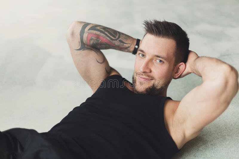 Young man fitness workout, cross crunches for abs stock photography