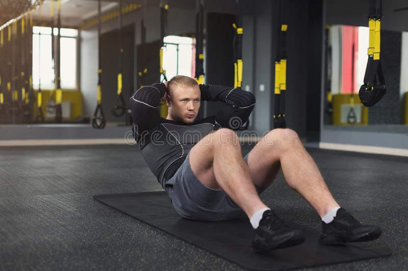 Young man fitness workout, sit-up crunches for abs. Young cheerful man workout in fitness club. Portrait of caucasian guy making exercise, sit-ups and crunches stock photography