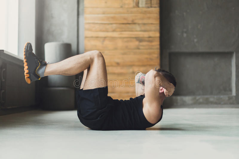 Young man fitness workout, sit-up crunches for abs royalty free stock image