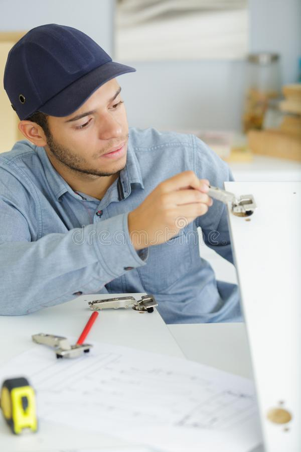 Young man fitting wardrobe in kitchen cabinet. Man stock photos