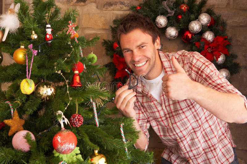 Young man fixing Christmas tree lights stock photography